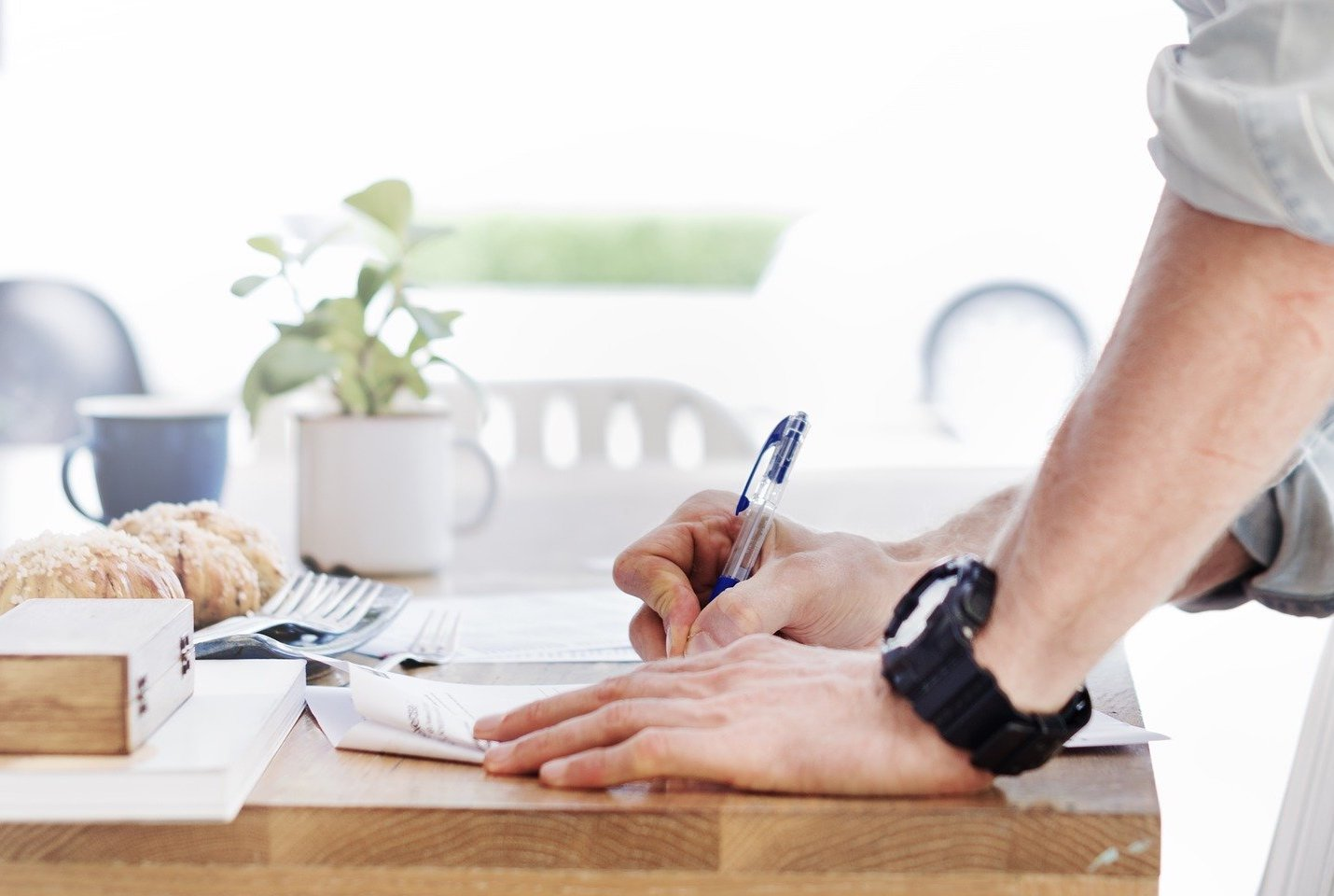 A home seller writes on a contract with a pen at their table.
