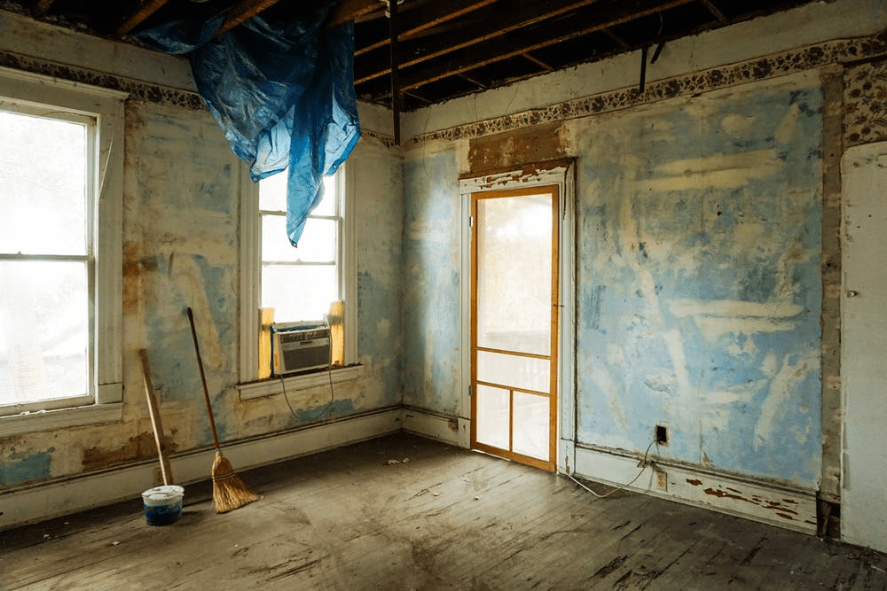 The interior of a distressed home. The walls have been stripped bare, there is a tarp handing from the ceiling rafters, and it is very dirty.